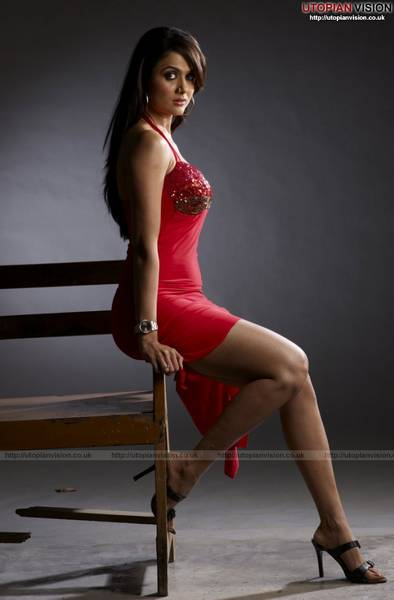 Amrita Arora wearing a red dress sitting on a bench